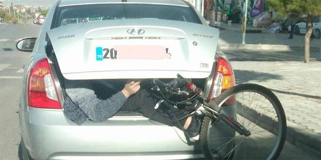 Bisikletiyle birlikte otomobilin bagajına bindi
